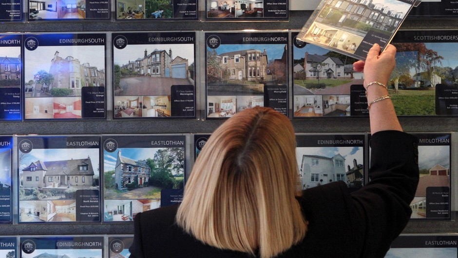 A woman looking at houses for sale at a Scottish estate agent