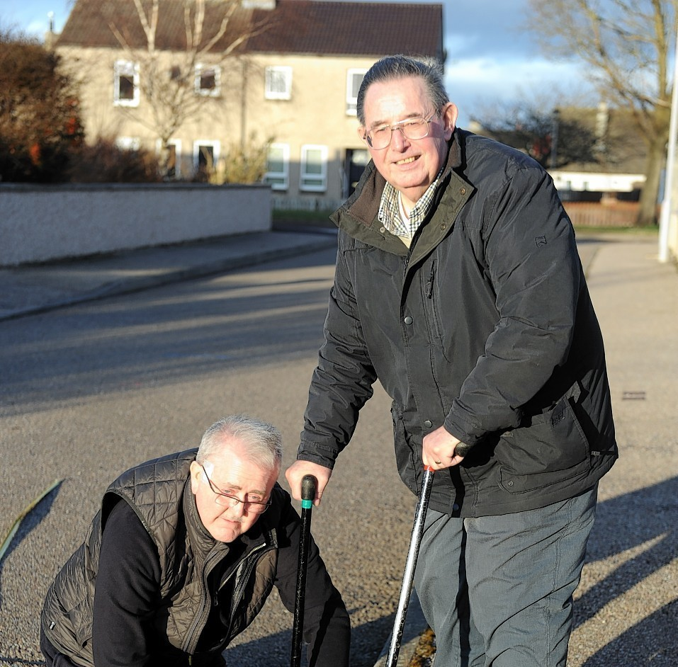 John Hamilton, left, and Robert Murdoch, right, measuring the road width in Halliman Way
