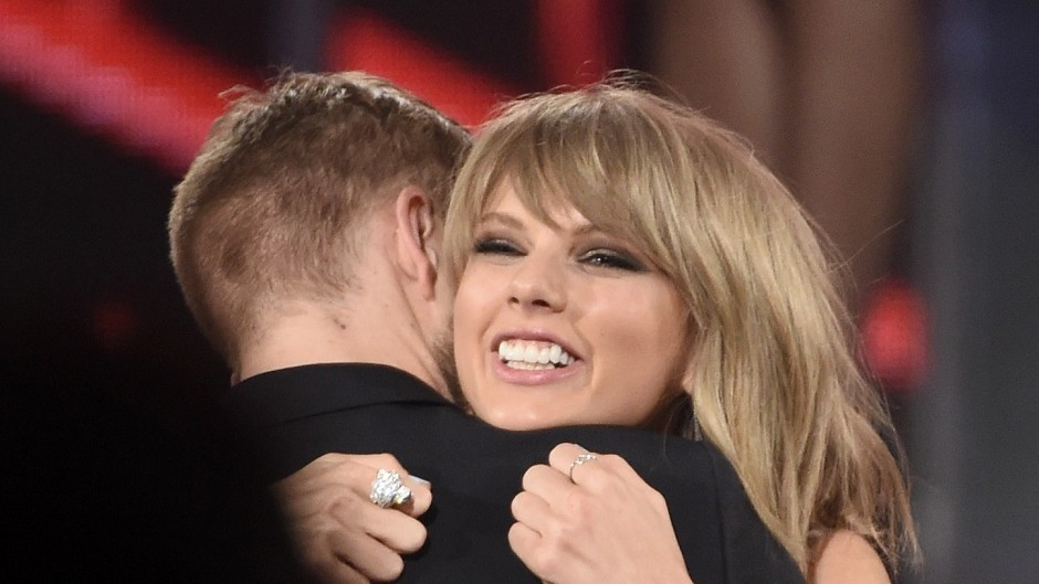 Taylor Swift hugs Calvin Harris at an awards ceremony.