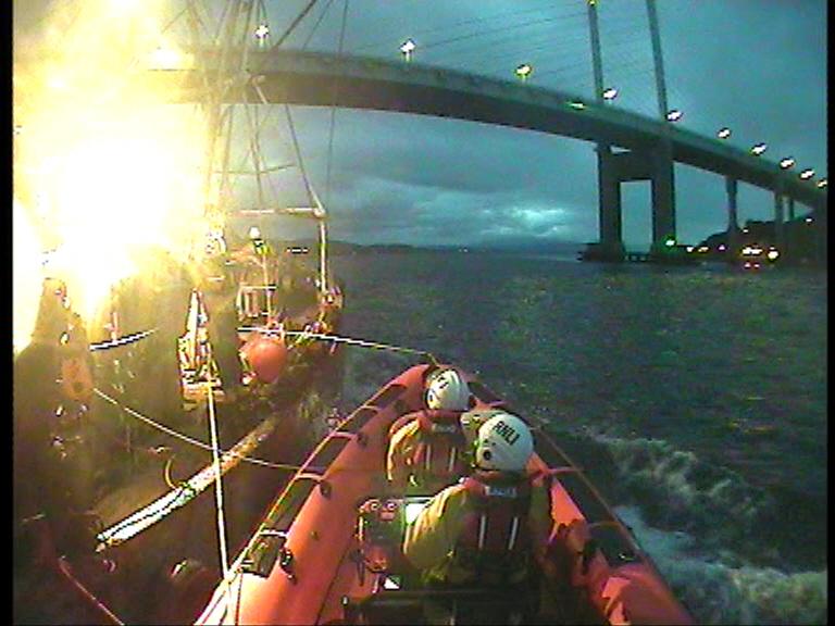 RNLI Kessock come under The Kessock Bridge with fishing vessel alongside