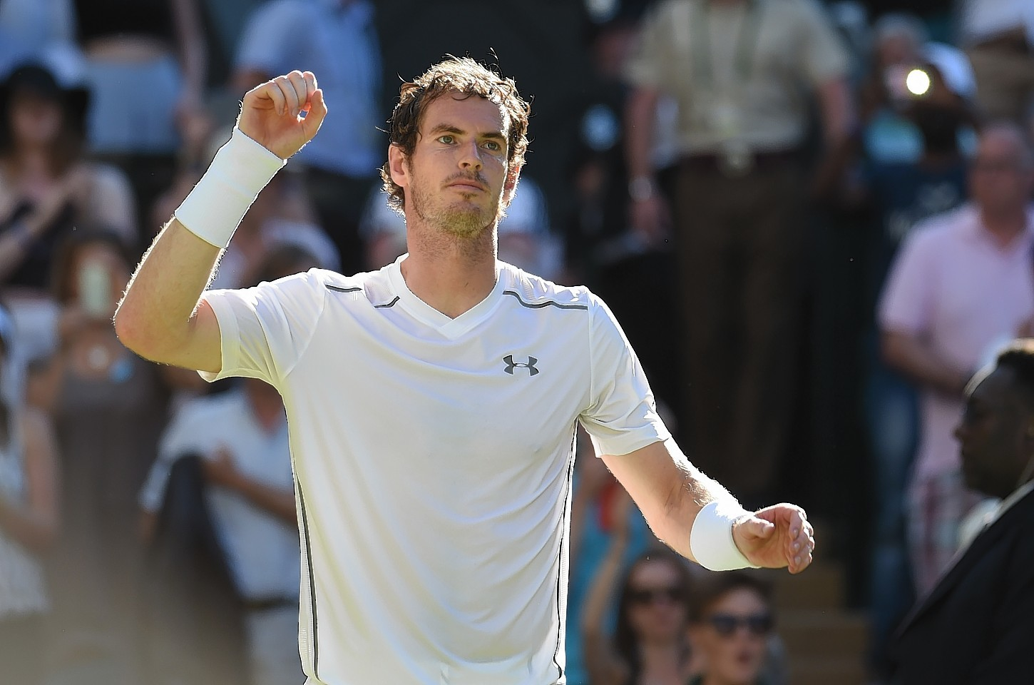 Andy Murray salutes the fans at Wimbledon as he defeats Mikhail Kukushkin by three straight sets.