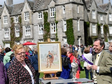 Balmoral housekeeper Sheena Stuart and expert Alastair Dickenson with a painting and a silver on bronze statue of Queen Victoria's piper William Ross.