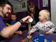 Martin McMullen from the PlayTalkRead bus plays in the sandpit with Madison Fisher
