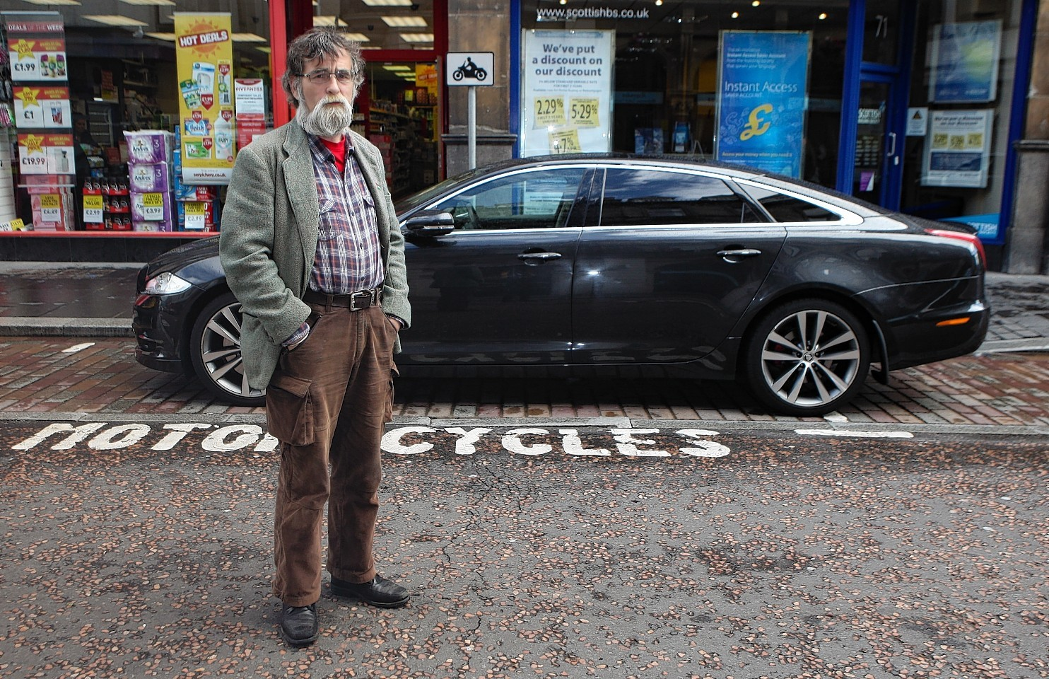 Highland Councillor Donnie Kerr with a car parked in a motor cycle bay on Queensgate, Inverness.