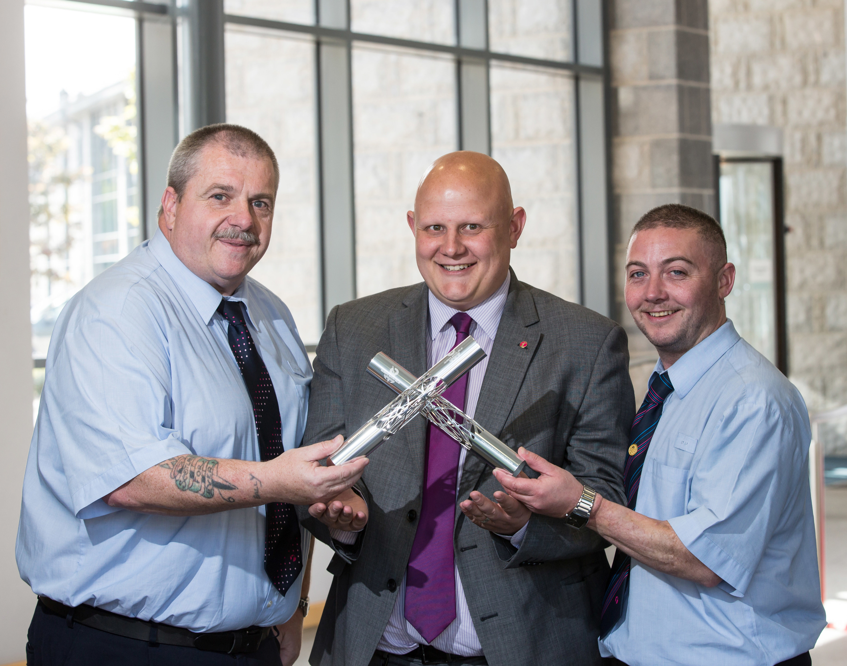 PICTURES FOR YOU FIRST MAGAZINE AT ABERDEEN BUS DEPOT. PICTURE SHOWS DRIVERS ANDREW BALLANTYNE (LEFT) AND SHANE MITCHELL (RIGHT) BEING PRESENTED WITH COMMEMORATIVE BATONS BY ABERDEEN MD DAVID PHILLIPS (CENTRE)AFTER THEY RAN IN THE COMMONWEALTH GAMES RELAY.