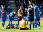 Gary Warren lies on the pitch as Stephen Pearson is shown a yellow card for his challenge