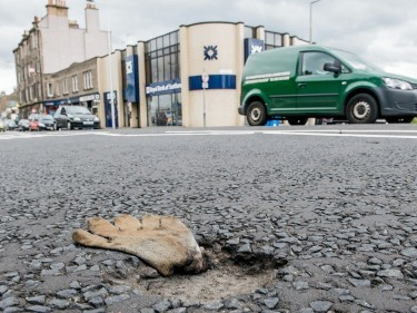 A pothole caused by workmans Glove after the road was closed for nearly a month for resurfacing in the Corstorphine area of Edinburgh