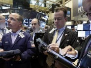 Traders gather at a post on the floor of the New York Stock Exchange (AP)