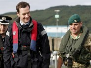 George Osborne (centre) arrives at the jetty of the Royal Navy's submarine base at Faslane