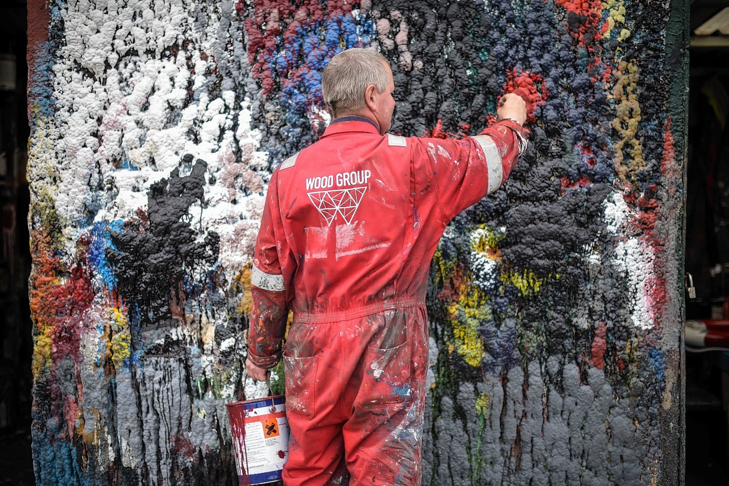 Painter Adrian Buchan cleans his brush on a wall at W Bruce Ship Painters in Fraserburgh,