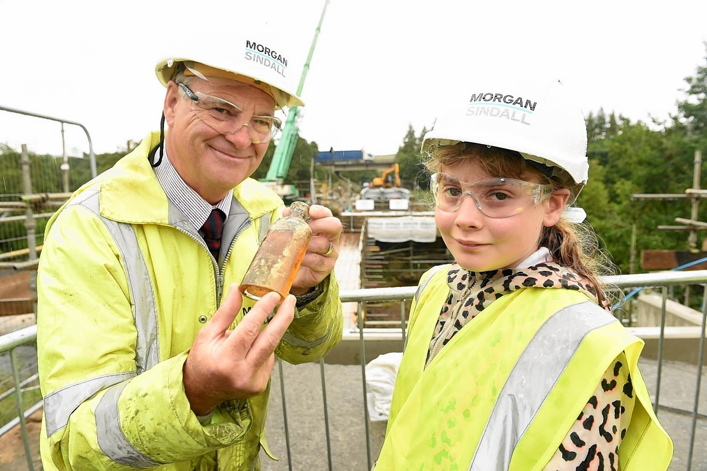 Project Manager Eric McAskill with primary seven pupil Zara MacNiven, Kingussie Primary school with the bottle of whisky removed from the time capsule.