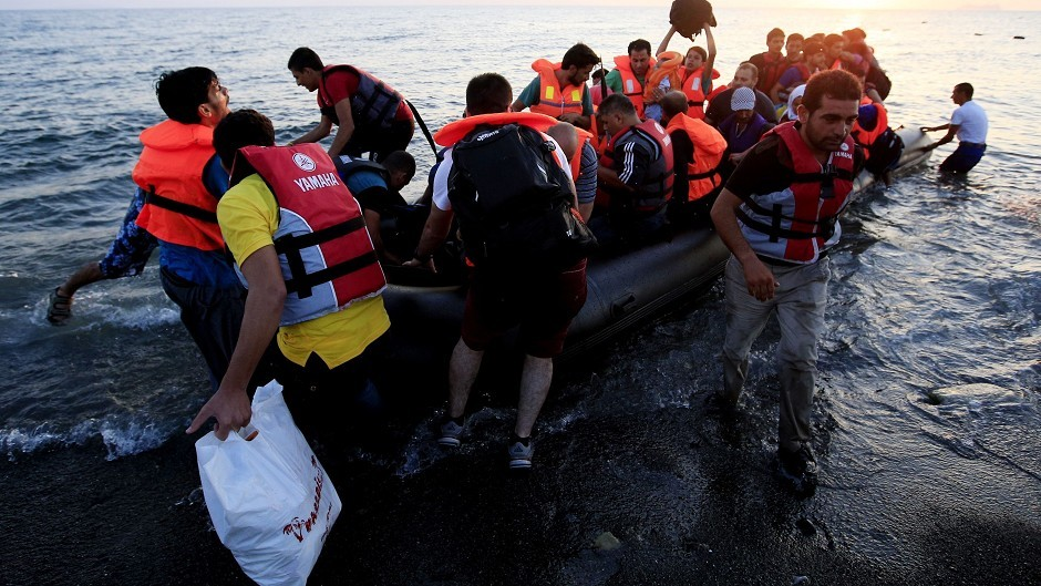 Refugees in a rubber dinghy arriving on the beach at Psalidi on Kos