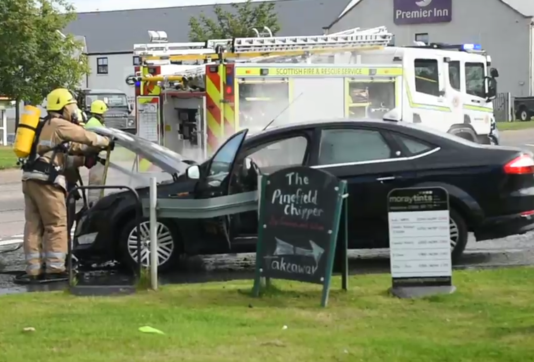 Firefighters battle the car fire in Elgin on the A96