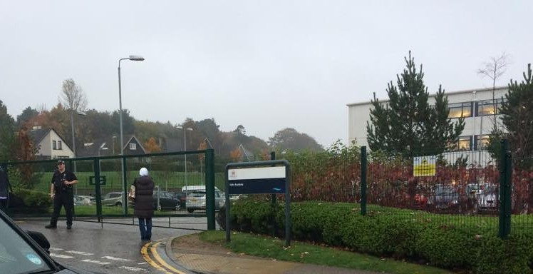 A police officer stands guard outside the school