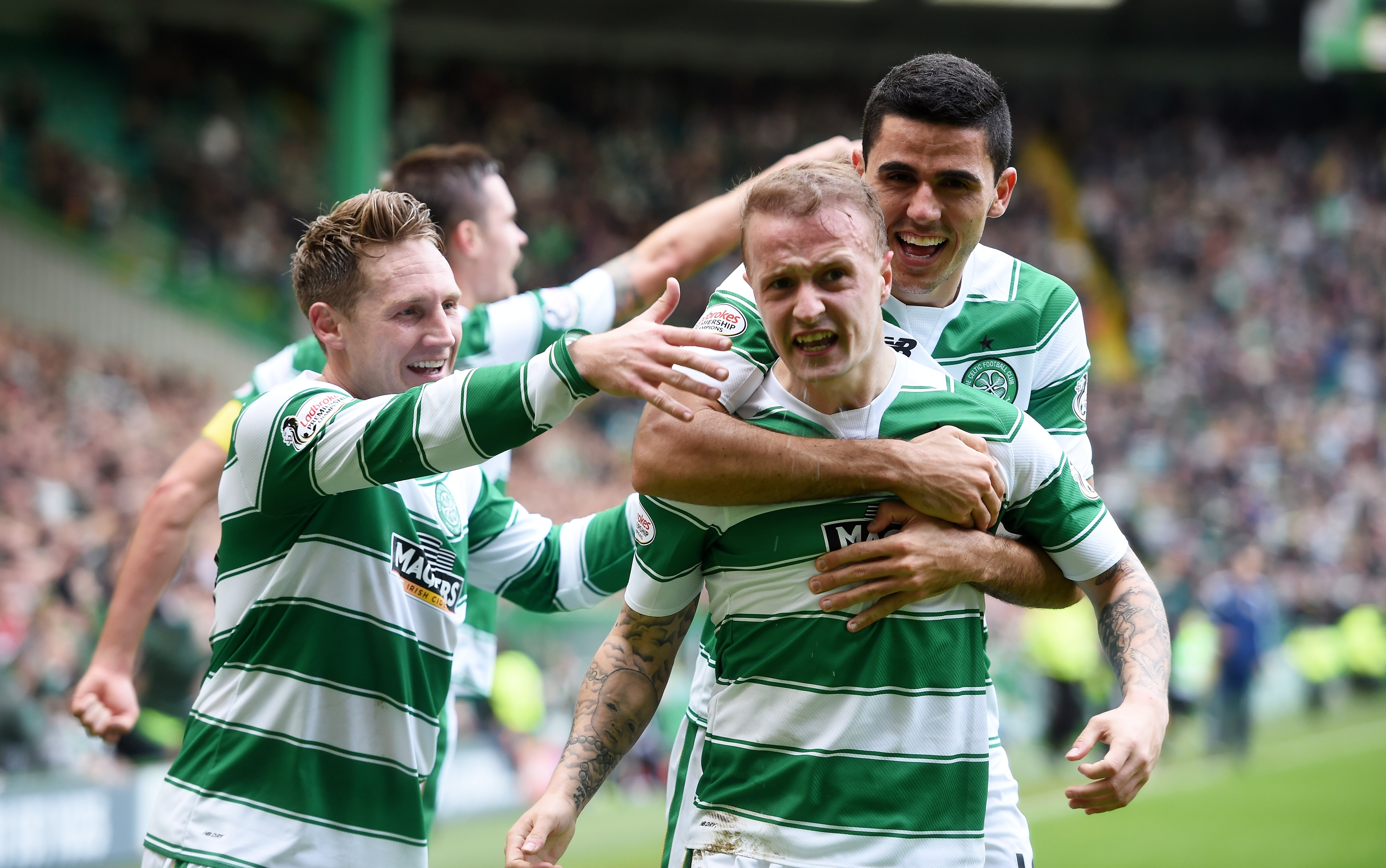 Celtic's Leigh Griffiths celebrates scoring from the spot with team-mates Tom Rogic (right) and Kris Commons