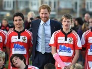 Prince Harry poses for a photograph with a members of a youth team during a visit to Paignton Rugby Club in Devon