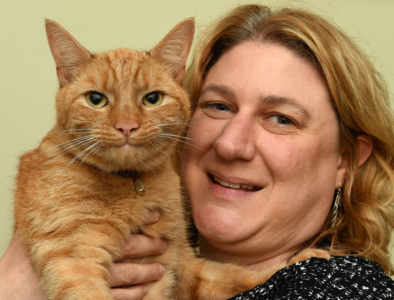 Helen Costin with her cat, Toffee, after he got miraculously stuck on the roof of a three-storey Aberdeen building