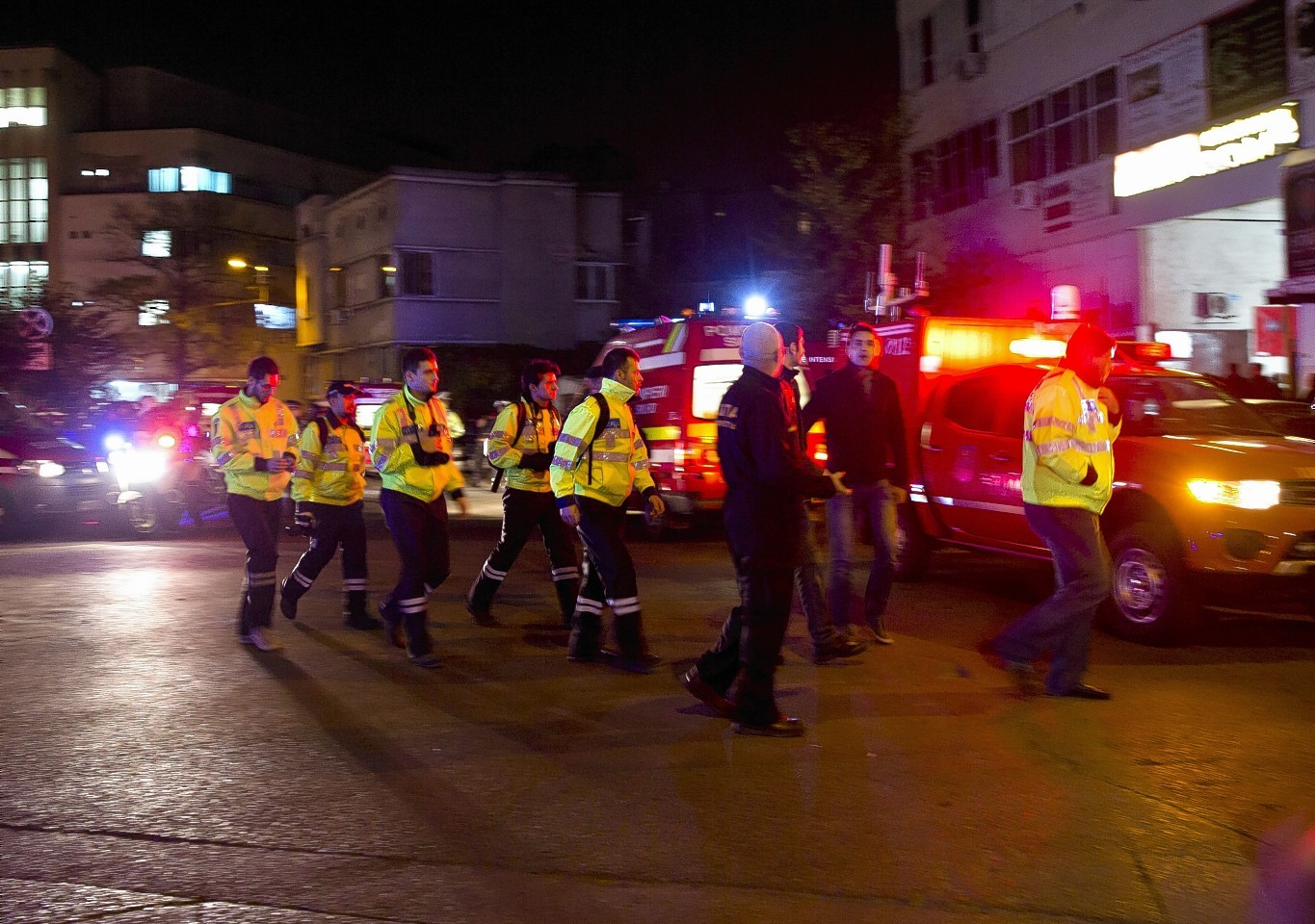 Emergency workers walk outside the scene of an explosion that occurred in a club in Bucharest