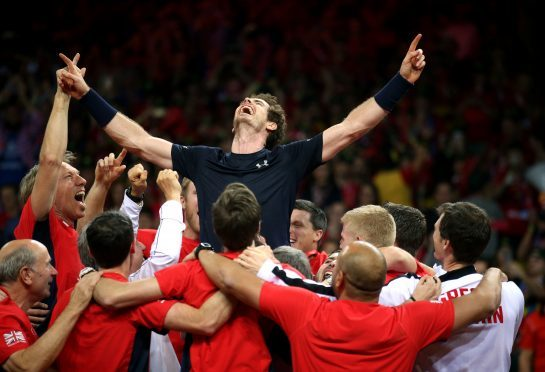 Great Britain's Andy Murray is mobbed by his team-mates after beating David Goffin during day three of the Davis Cup Final at the Flanders Expo Centre