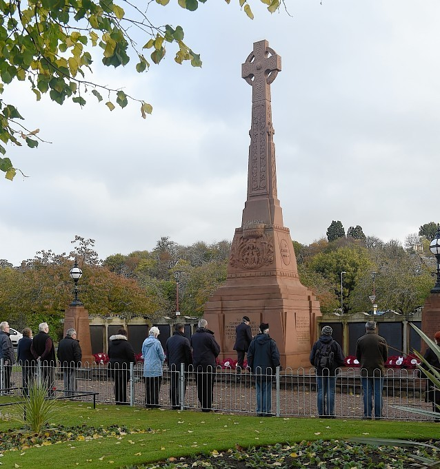Members of the public observe the silence at the Cenotaph in Cavell Gardens