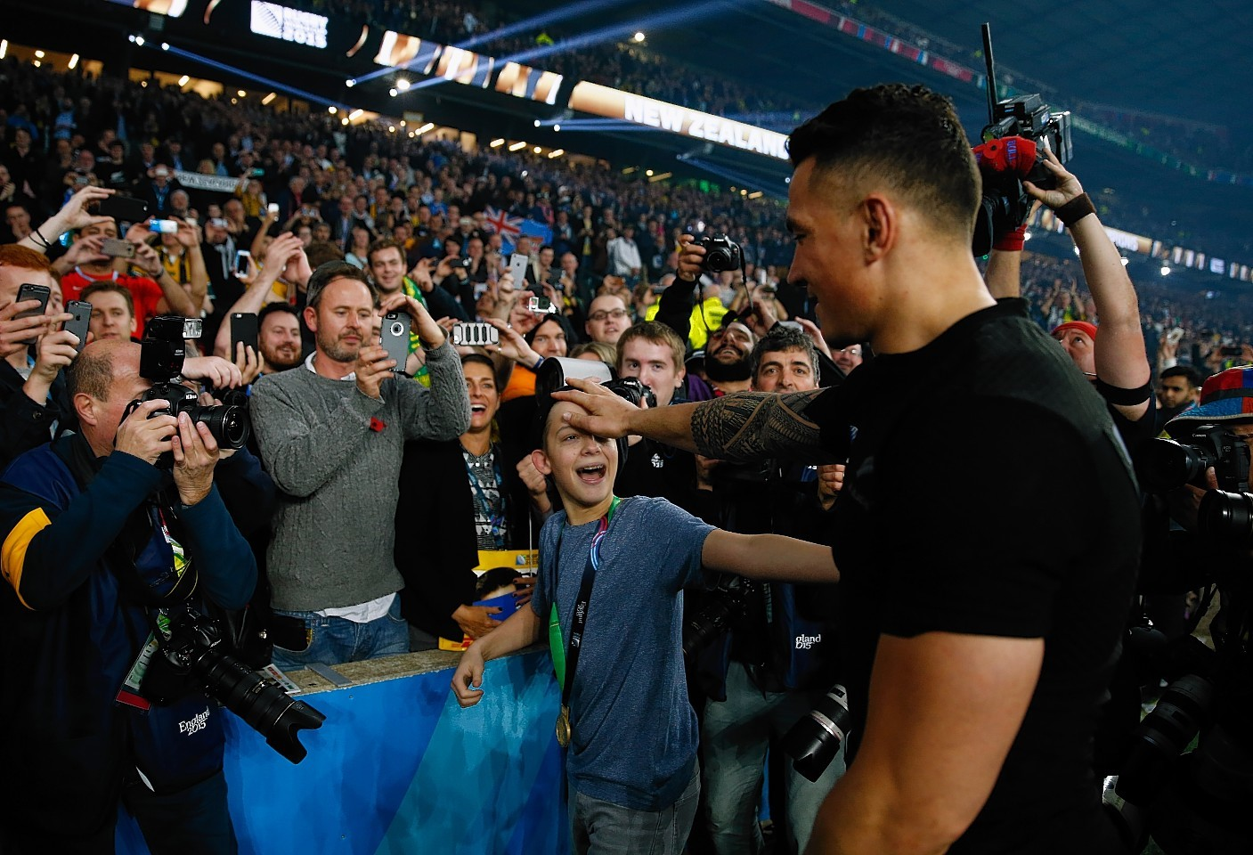 LONDON, ENGLAND - OCTOBER 31:  Sonny Bill Williams of New Zealand gives his winners medal to a young fan following the 2015 Rugby World Cup Final match between New Zealand and Australia at Twickenham Stadium on October 31, 2015 in London, United Kingdom.  (Photo by Mike Hewitt/Getty Images)