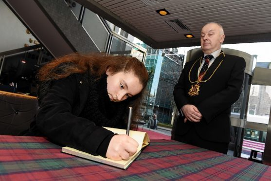 First member of the public to sign a book of condolence for victims of the Paris attacks, Emilie Girard, with Lord Provost George Adam looking on at Aberdeen Town House. Picture by Kevin Emslie