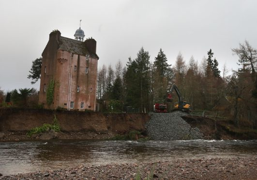 Rocks and boulders are moved to protect the shoreline on the River Dee