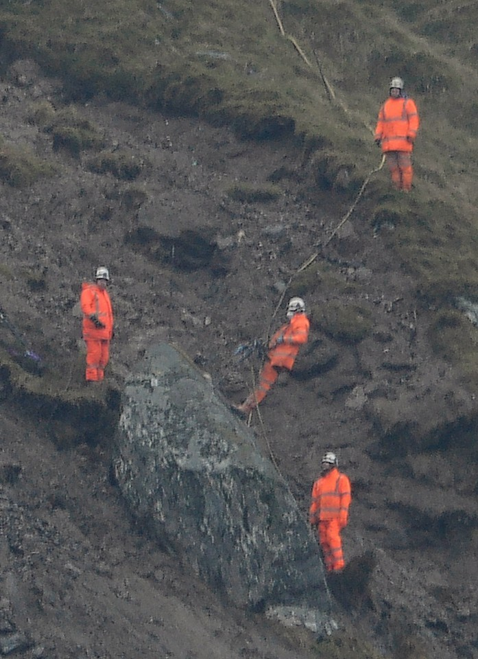 Workmen prepare to detonate the huge boulder above the Rest and be Thankful pass near Arrochar