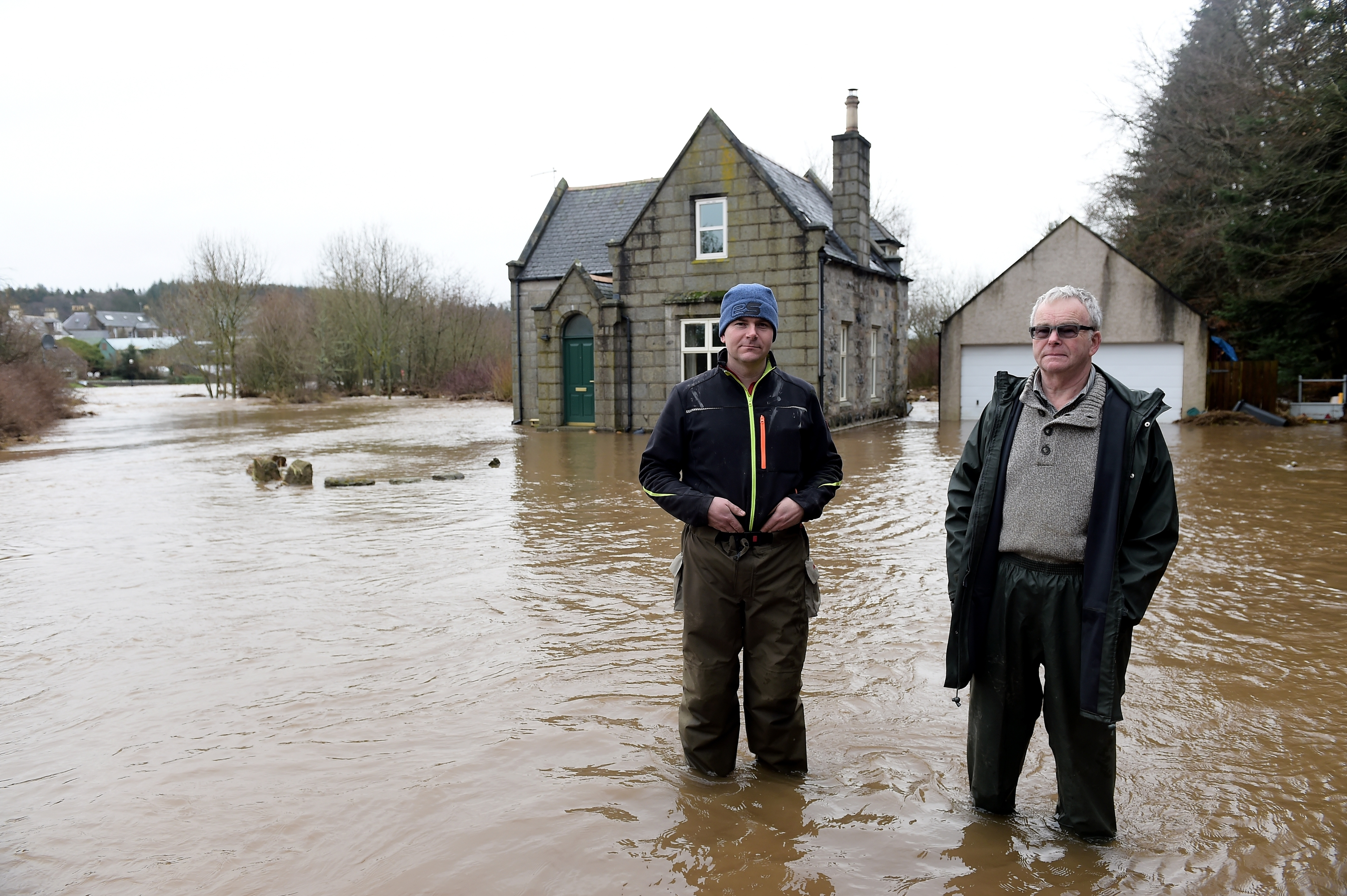 The River Ythan has burst it's banks at Ellon. The home of George Thomson on the banks of the Ythan near the old bridge which was flooded last night. George (right) is pictured with his son Craig Thomson.