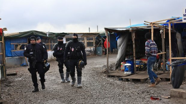 French police officers patrol in the migrant camp in Calais (AP)
