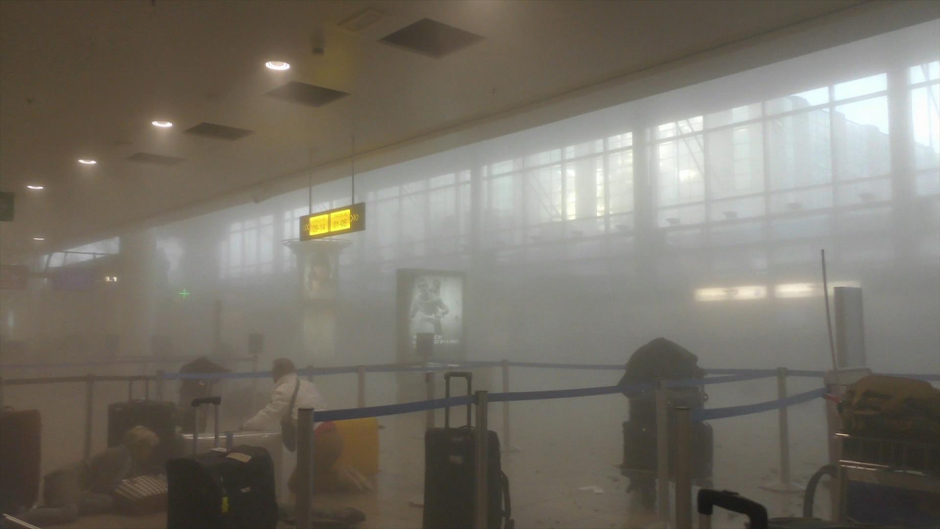 An unidentified traveller gets to his feet in a smoke filled terminal at Brussels Airport (Ralph Usbeck/AP)