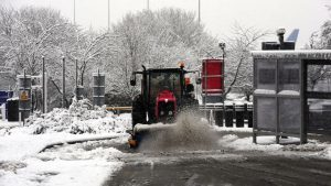 A tractor clears a snow-covered road