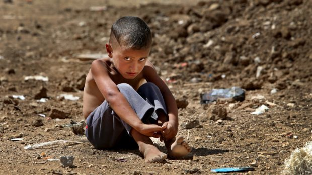 A Syrian refugee boy sits on the ground at a temporary refugee camp in the eastern Lebanese town of Al-Faour (AP)