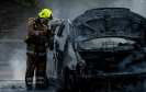 A firefighter damps down the burnt out car in Fort William