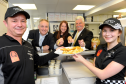 Back L-R: Richard Lochhead MSP, Sarah Medcraf, project director developing young workforce in Moray, and Jim Oag, director Highlands and Islands Services, reaching for the fish and chipsmade by Darren Boothroyd, left, owner of the business, and Elise Boothroyd, right, who works in the shop, at Fochabers Fish Bar after it was presented with an award for Investing in Young People. Picture by Gordon Lennox