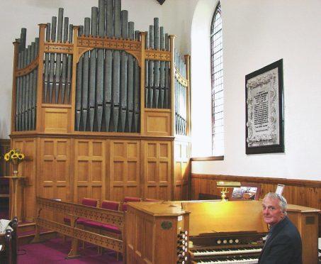 Organist John Crombie with the impressive organ at Kingussie Parish Church