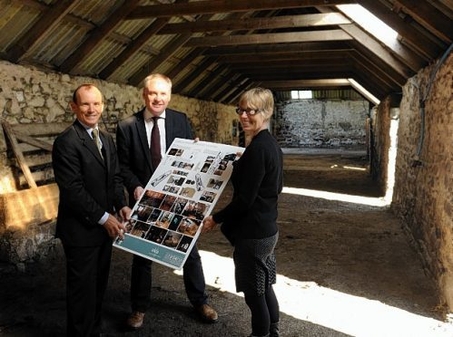 Grant Gordon, chairman of the Cabrach Trust, left, and Sue Savege, executive director of the Cabrach Trust, right, show details of the interior to Richard Lochhead, MSP, centre.
