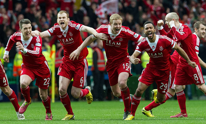 Aberdeen players sprint to celebrate with penalty shoot-out hero Adam Rooney (not pictured) as they clinch the Scottish League Cup Fina