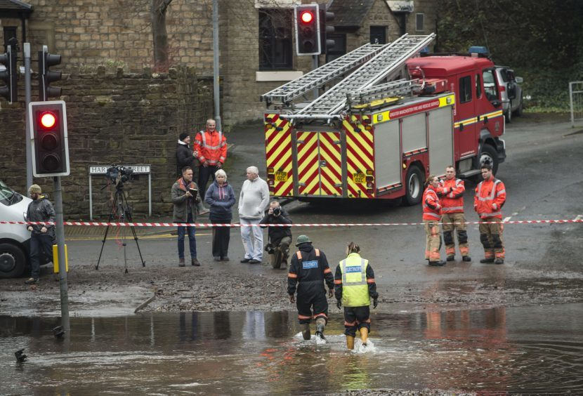 Electricity workers outside a property that was flooded in Millbrook near  Stalybridge in Greater Manchester after heavy rain overnight