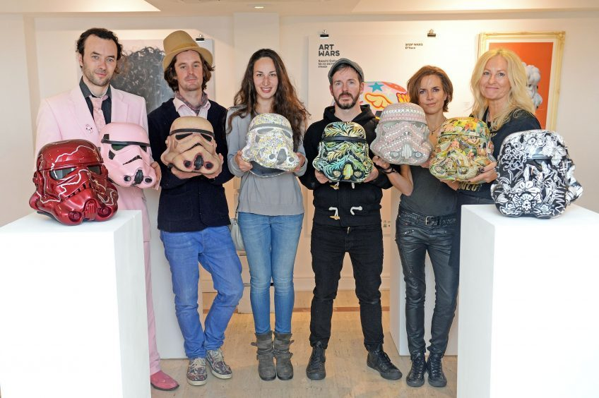 (left to right) Artists Nick Player, Ben Moore, Polina Vasenkova, Carne Griffiths, Miranda Donovan and Agnetha Sjögren with Stormtrooper helmets they designed