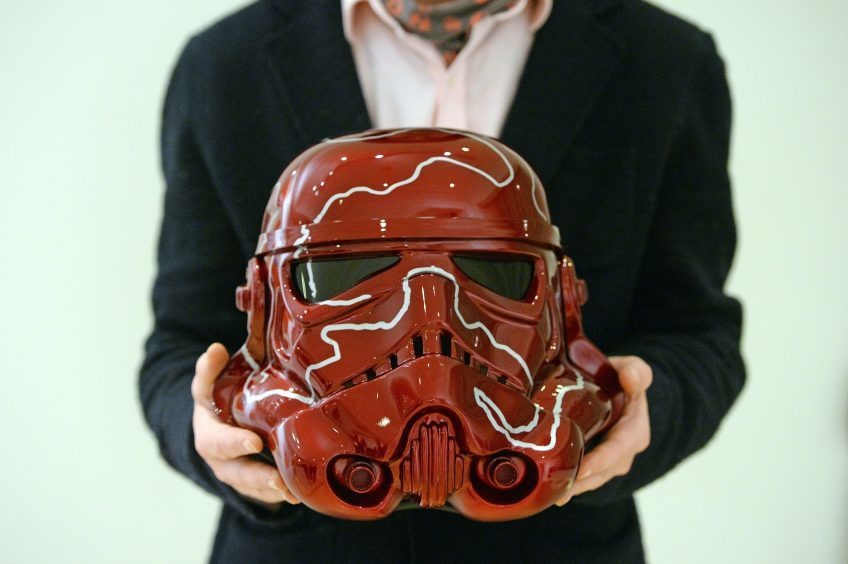 Curator Ben Moore holds a Stormtrooper helmet by artist Sir Anish Kapoor