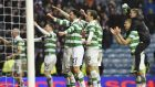 Celtic players celebrate with fans after winning at Ibrox