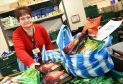 Volunteer Angela Wilson packing food bags at Cfine.
