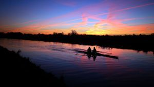 A boat crew works out as the sunrises along the river Cam in Cambridge