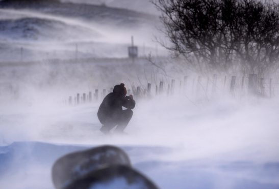 Tour guide Neil McLennan tries to capture a snow drift on his mobile phone on the A9 at the Drumochter Pass