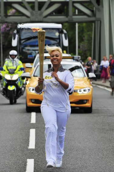 Emeli Sande carries the Olympic Flame on the Torch Relay leg from Glencoe to North Ballachulish in 2012.