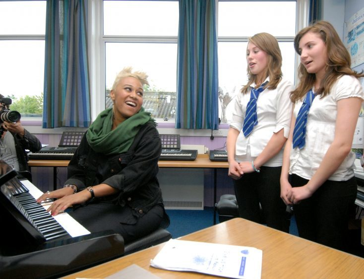 Emeli leads choir practice during a visit to her old school in 2011.