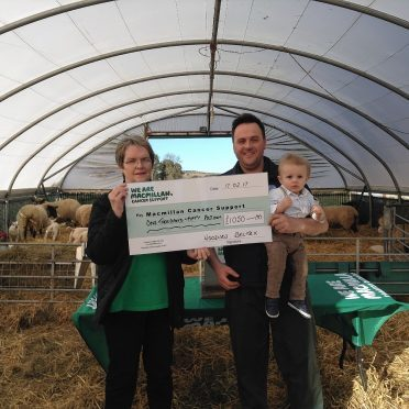 Margo Stewart receiving a cheque from Stuart and Murray Wood
