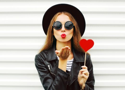 Fashion woman with red lips sends air kiss lollipop heart