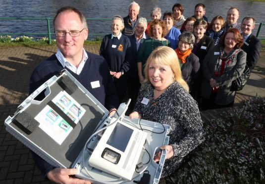 Representatives of the charities with, at the front, Ullapool Health Centre GP Richard Weekes and Great Wilderness Challenge secretary Pat Ross, with a £6,000 ultrasound scanner donated to the health centre.